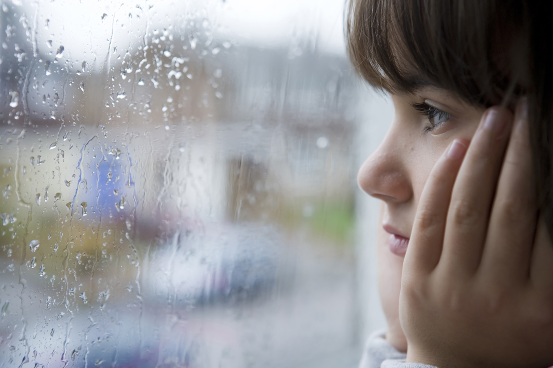 Kid Stares out Window on Rainy Day